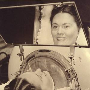 "Jane Boyle Needham, quite literally ""looking up"", into the mirror attached to her iron lung, which allowed her to view her world."